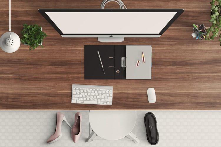 Escritorio de madera con zapatos y computadora